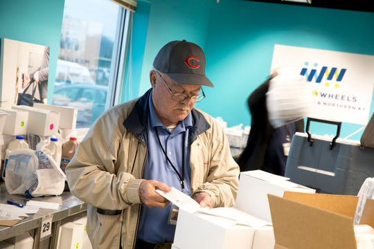 John Simon, a Meals on Wheels driver, prepares daily deliveries of food to clients at the Meals on Wheels packaging facility in Lower Price Hill on Wednesday, March 18.