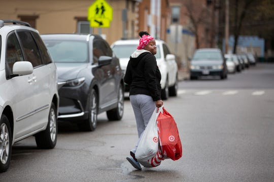 Renee Bates, mother of eight, leaves the Oyler Madhatter Pantry in Lower Price Hill, Wednesday, March 18, 2020. Cincinnati Public Schools is handing out food to students from 11 - 1 p.m. on Mondays, Wednesdays and Fridays. During the same hours, the pantry is offering supplies, including school supplies to families, with or without children. Bates said not knowing how long this would continue is scary, but the pantry 'is a real good thing' for families. Due to the new coronavirus, schools and many other businesses are closed