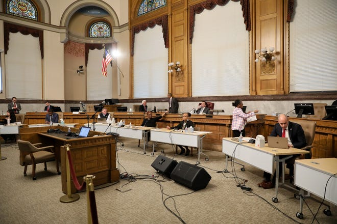 Cincinnati city council members sit apart as a safety precaution amid the new coronavirus outbreak, Wednesday, March 18, 2020, at City Hall in Cincinnati. There was no public comment either.