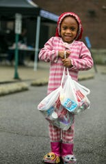 Teeyana Williams, 5, a kindergartner at Oyler School in Lower Price Hill picks up two days worth of lunches from the school, Wednesday, March 18, 2020. Cincinnati Public Schools are handing out food from outside schools from 11 - 1 p.m. Monday, Wednesday and Friday. With the new coronavirus, schools and many other businesses are closed, but help is still there for children who depend on the schools for their daily mea