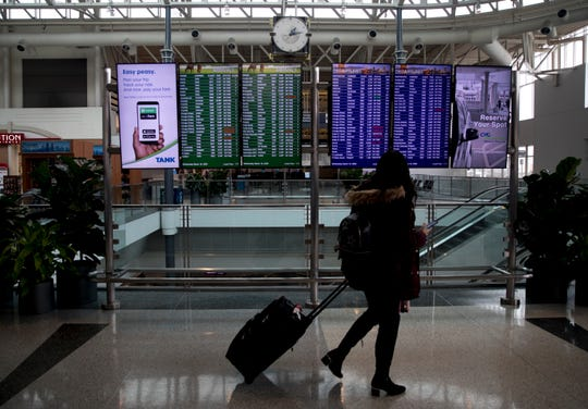 A traveler looks at the departure boards before heading through security at Cincinnati/Northern Kentucky International Airport on Wednesday, March 18, 2020, in Hebron, Ky.