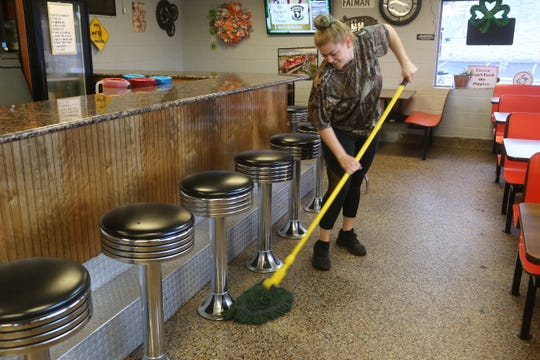Kelly's Big Burgers employee Pamela Dudley mops the floor as she waits for customers in their Clarksville diner amid the coronavirus crisis on March 17, 2020.