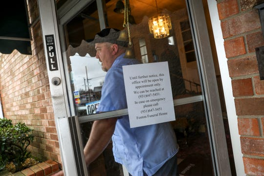 A sign in the front glass window advises guests and visitors of the more limited hours and interaction taking form at Foston Funeral Home in Clarksville, Tenn., on Wednesday, March 18, 2020.