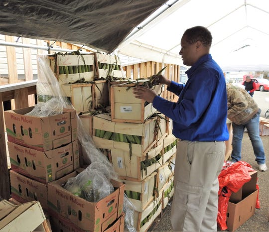 Pastor Stan Braxton opens a crate of corn during food distribution Wednesday at the Upper Room Assembly and Worship Center. He consulted with local officials on continuing the program this month, which gives out more than 40,000 pounds of food to 275 families on average.