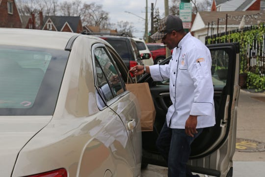 Table No. 2 chef-owner Omar Mitchell delivers a curbside carryout order outside the northwest Detroit restaurant Tuesday, March 17, 2020, a day after Gov. Whitmer limited all restaurant operations in the state to delivery and takeout only over coronavirus concerns.