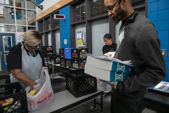 Food services employee Cora Johnson packs up food for Detroit Public Schools program supervisor for mentoring Brett Jordan to hand deliver school supplies and a bag of breakfasts and lunches prepared at David L. Mackenzie Elementary-Middle school Wednesday, March, 18, 2020. DPD has set up a Grab and Go curbside pickup system for families needing educational supplies and food due to the COVID-19 threat.