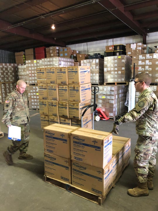 Members of the Michigan Army National Guard help assemble and load personal protective gear to distribute to local health departments in response to the coronavirus outbreak on Wednesday, March 19.