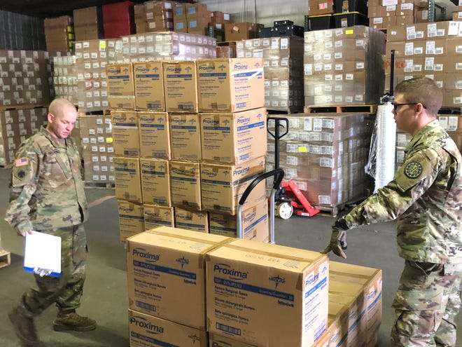 Members of the Michigan Army National Guard help assemble and load personal protective gear to be distributed to local health departments in response to the coronavirus outbreak.