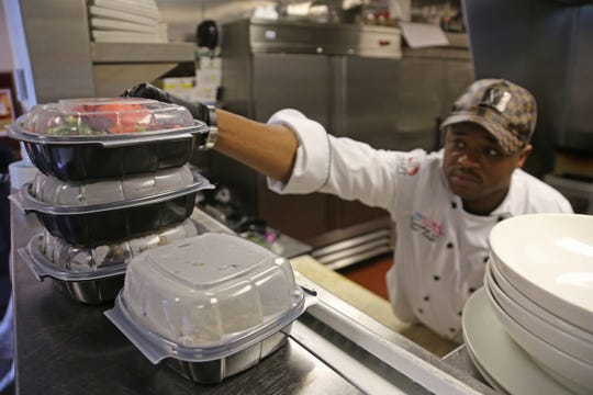 Table No. 2 chef-owner Omar Mitchell prepares an order for delivery on March 17, 2020, a day after Michigan Governor Gretchen Whitmer limited all restaurant operations in the state to delivery and takeout only over novel coronavirus concerns.