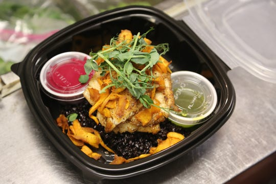Pan-seared barramundi with black rice and beet puree gets packaged for a carryout order at Table No. 2 in northwest Detroit Tuesday, March 17, 2020, a day after Michigan Governor Gretchen Whitmer limited all restaurant operations to delivery and takeout only over novel coronavirus concerns.