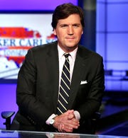 """In this March 2, 2017 file photo, Tucker Carlson, host of """"Tucker Carlson Tonight,"""" poses for photos in a Fox News Channel studio, in New York. Carlson says he felt a moral obligation to meet with President Donald Trump to warn him about the seriousness of coronavirus. He told Vanity Fair that while he didn't feel it was his role, his wife convinced him to request the meeting, which took place on March 7."""