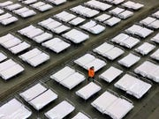 Workers arrange beds in a convention center that has been converted into a temporary hospital in Wuhan in central China's Hubei Province, Tuesday, Feb. 4, 2020. China said Tuesday the number of infections from a new virus surpassed 20,000.