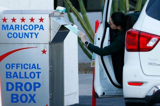 An Arizona voter drops off a ballot Tuesday in Phoenix.