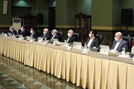 In this photo released by the official website of the Office of the Iranian Presidency, cabinet members wearing face masks attend their meeting in Tehran, Iran, Wednesday, March 18, 2020.