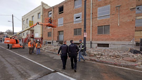 Police officers walk pass rubble after an earthquake Wednesday in Salt Lake City.