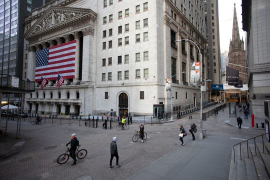 A few people walk on Wall Street in front of the New York Stock Exchange, Wednesday in New York.