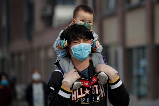 A man carries a toddler on his shoulders as both wear protective face masks to help prevent the coronavirus outbreak walk on a street in Beijing, Wednesday, March 18, 2020. As the pandemic expanded its reach, China and South Korea were trying to hold their hard-fought gains. China is quarantining new arrivals, who in recent days have accounted for an increasing number of cases, and South Korea starting Thursday will increase screenings of all overseas arrivals.