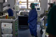 In this March 16, 2020, photo, doctors work in the intensive care unit of the Brescia hospital, Italy. Hospitals in northern Italy are struggling to make room for the onslaught of coronavirus patients.