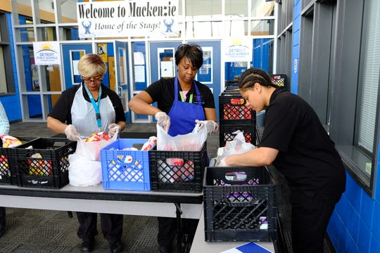 Administrative staff helping pack take-home food at David L. Mackenzie Elementary-Middle School Wednesday.