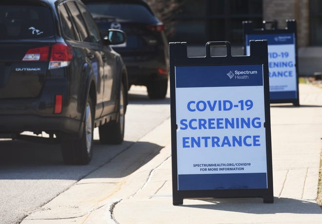 Cars line up at a drive-up COVID-19 specimen collection center Tuesday, March 17, 2020, at the Spectrum Health Lakeland Center for Outpatient Services in St. Joseph, Mich.