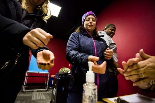 Sharon Trask and other voters use hand sanitizer as they stand in line to vote at Lincoln Lodge Polling station, 1st ward, Tuesday in Chicago.