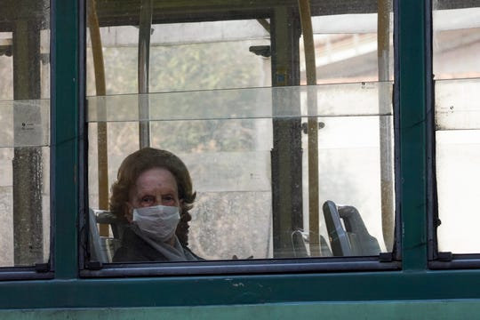 A woman wears a protective mask as she rides in a tram, in Rome, Wednesday, March 18, 2020. For most people, the new coronavirus causes only mild or moderate symptoms.