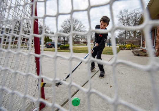 Ian Mearns, 9, practices his shot in front of his home in Grosse Ile. The Meridian Elementary School fourth-grader is a member of the Belle Tire Bombers hockey team and was trying to get in some practice after his season was postponed due to the coronavirus pandemic.