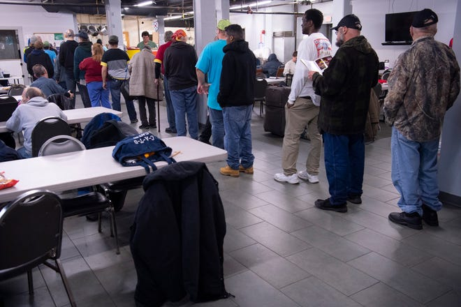 Homeless guests at the United Caring Services in Evansville line up for dinner Wednesday evening, March 18, 2020. Turkey sandwiches with soup, salad and a cupcake or cookie were the offering this night. With most of the volunteers at the facility being in the most susceptible age range to contract the coronavirus COVID-19, the homeless guests are not only doing the cooking, but the serving and cleaning at the shelter.
