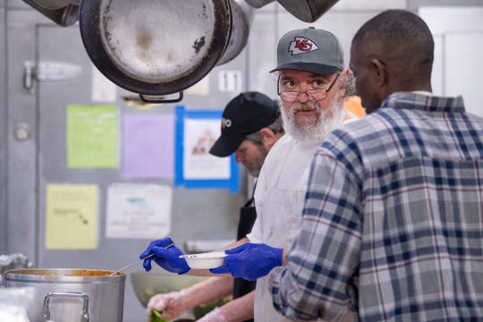 Bill Myrick, center, and Derrick Gulley keep the work fun by joking around at the United Caring Services in Evansville Wednesday evening, March 18, 2020. With most of the volunteers at the facility being in the most susceptible age range to contract the coronavirus COVID-19, the homeless guests are not only doing the cooking, but the serving and cleaning at the shelter.