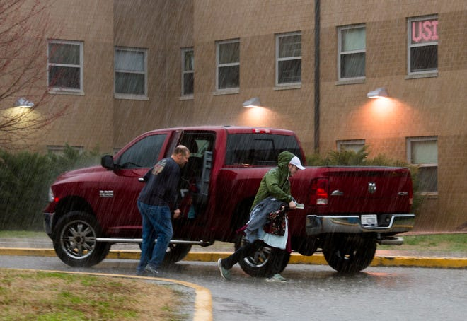 Conley Long , left, shuts a door on his truck as University of Southern Indiana freshman Michael Bingham, right, rushes to the other side with clothes in hand while rain pours at USI in Evansville, Ind., Wednesday morning, March 18, 2020. Bingham was moving out of USI's Governors dorm after the university announced Tuesday they were going to solely online instruction through the end of the school year and students who live on campus must move out by March 22nd due to the spread of COVID-19.