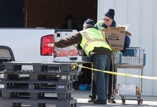 Fond du Lac Food Pantry volunteers Lyle Birschbach and Jim Stewart load a vehicle outside due to concerns of the COVID-19 virus Tuesday at the Fondy Pantry in Fond du Lac.