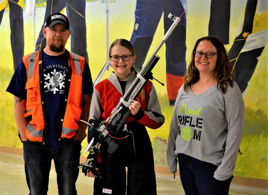 Matt Muzik, left, is forming a Youth Marksmanship Team in rural Green Springs. He has taught several area youth to shoot, including his daughter, Claudia, shown here with the air rifle she competed with at Camp Perry on March 14. Matt's wife, Alana, right, also supports their daughter's sport and is helping Matt form the team.