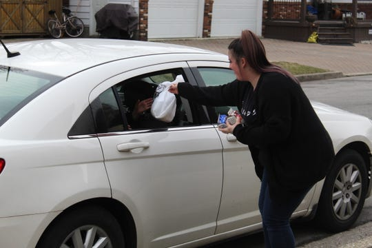 Mariah Parish, a preschool paraprofessional, hands food to families at Stamm Elementary Wednesday.