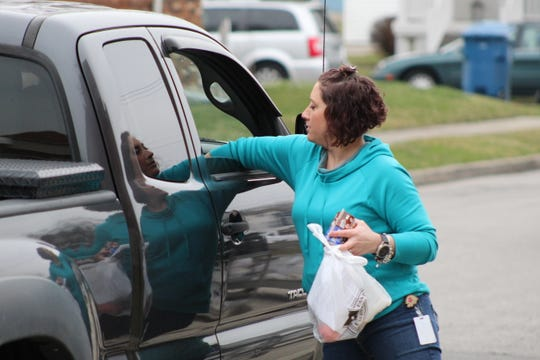 Dawn Mellott, an intervention tutor, passes out food to families at Stamm Elementary, which has closed due to the novel coronavirus pandemic.
