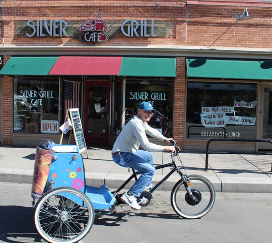 Silver Grill Cafe owner John Arnolfo sets off in a rickshaw to deliver cinnamon rolls and hand out takeout menus Wednesday. Arnolfo used the rickshaw to let people know the breakfast restaurant is still open for takeout, curbside pickup and delivery.