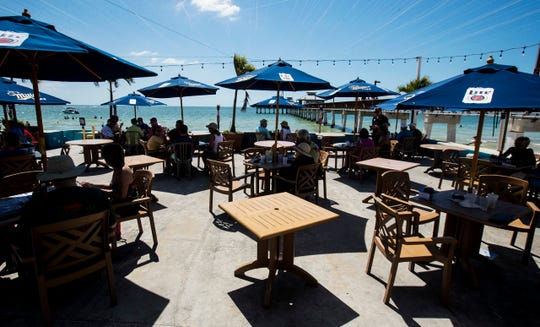 Empty tables sit between occupied ones at Pierside Grill and Famous Blowfish Bar on Fort Myers Beach on Wednesday March, 18, 2020. Restaurants are taking many more precautions amid the coronavirus pandemic including closing bars and restricting groups of more than 10 people to stifle the pandemic.