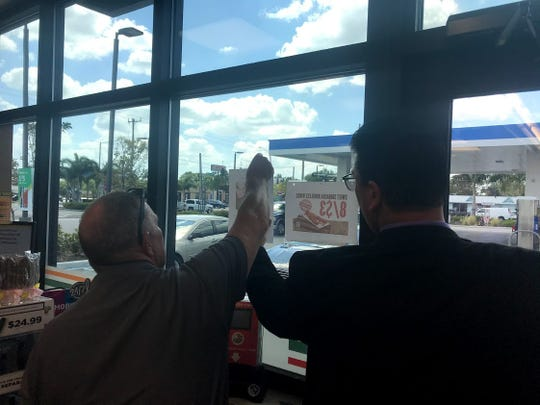 Fort Myers Police Cold Case Investigator Ed Haras (left) and Detective Vincent Doyle post a flyer at a 7-Eleven on Cleveland Avenue about Porter Albert who went missing in January.