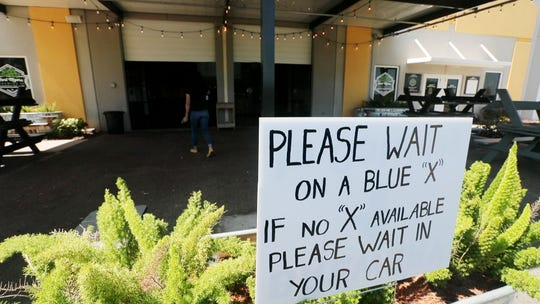 Fort Myers Brewing Co. asks that each person stands on a blue X while lining up for beer to-go from its taproom-turned-bottle-shop. The blue Xs are 6 feet apart in compliance with state mandates.