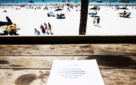 A sign at the Sable Palm Bar and Grill at the Lani Kai on Fort Myers Beach Wednesday March, 18, 2020 asks visitors to observe social distancing standards because of the coronavirus pandemic. Beaches across Lee County have since been closed due to the virus.