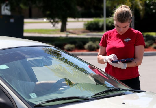 Faith Harris, a server at Skinny Dogz, takes an order in the restaurant's Gateway parking lot.