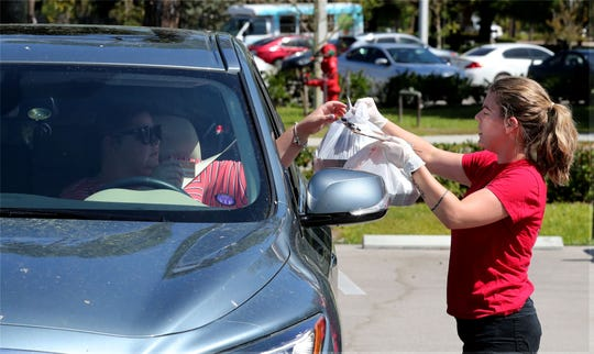 Faith Harris, a server at Skinny Dogs Brunchery, delivers food to a customer in their car Wednesday. The Gateway restaurant has closed its inside dining room and is offering curbside takeout due to COVID-19.