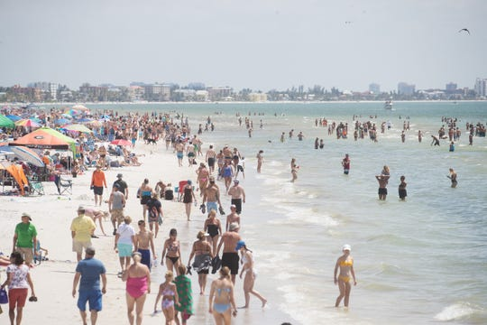 Visitors hang out on Fort Myers Beach Wednesday March, 18, 2020. Photographed from the Fort Myers Beach Pier looking south towards the Lani Kai resort and other restaurants and establishments.