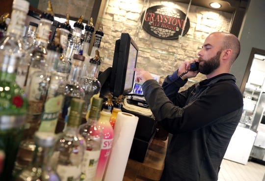 Lee Hoople, general manager and partner at Graystone Ale House in Ledgeview, enters a phone order for pickup of chicken wings and a sandwich into the computer system on Wednesday.
