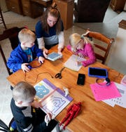 While Andrew Mulloy, principal of St. John the Baptist School, talks with teachers on the phone in another room, his wife, Laura, works with their three children — twins in kindergarten Gianna and Paul, and 3-year-old preschooler Aaron — using the learning materials and digital content teachers are providing while sitting at the family's kitchen table at their home on March 18, 2020 in Howard, Wis.