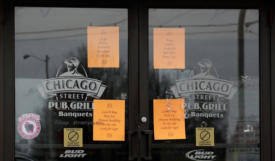 Signs on the door of Chicago Street Pub and Grill in De Pere tell customers that to-go orders are available from 4 to 8 p.m.