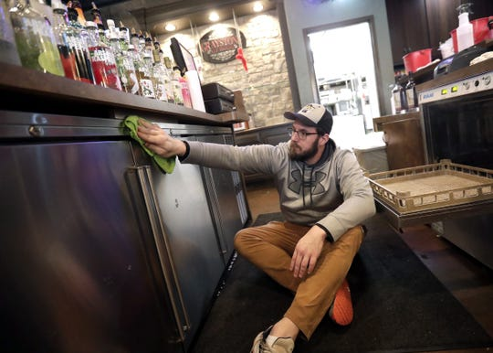 Wallace Bridges, assistant general manager at Graystone Ale House in Ledgeview, cleans the glass chillers on Wednesday.
