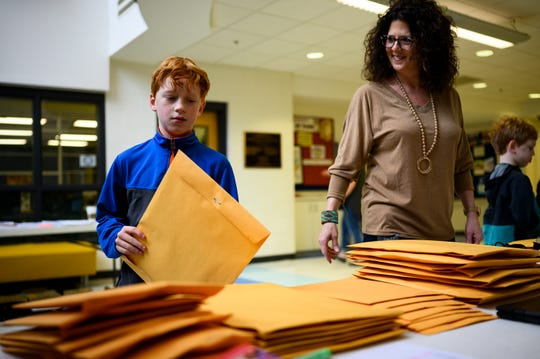 Fifth grader Owen Carroll picks up his school materials at Stone Academy Wednesday, March 18, 2020.