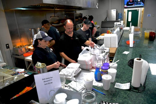 Employees assemble lunches at Arnold's for pickup in Anderson Wednesday, March 18, 2020.