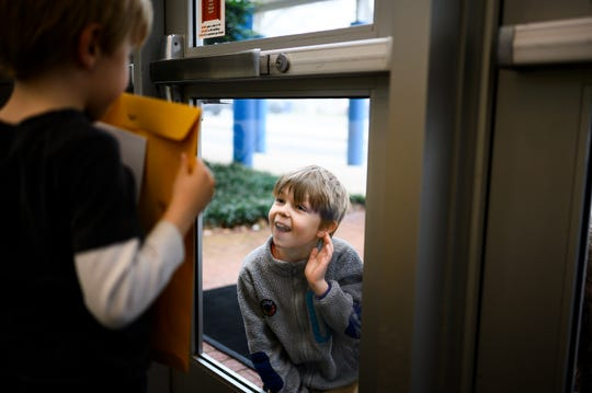 Second grader Noah Moon signals to his younger brother Isaac through a door window at the entrance of Stone Academy after Isaac picked up his school materials Wednesday, March 18, 2020.