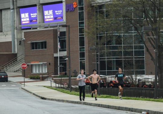 "Joggers run by digital message boards flashes ""Online Instruction COVID019 Update and online instruction through April 5"" near the IPTAY office at Memorial Stadium in Clemson Wednesday, March 18, 2020."